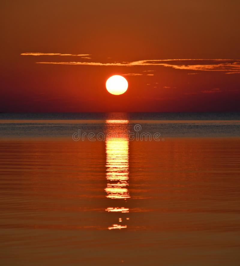 The sun is setting and evening is falling as hope rises. Sunset over the sea stock images