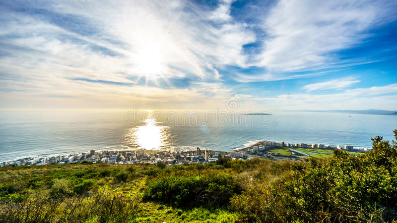 Sun setting over the Atlantic Ocean, Sea Point and Camps Bay. Viewed from Signal Hill at Cape Town, South Africa royalty free stock image