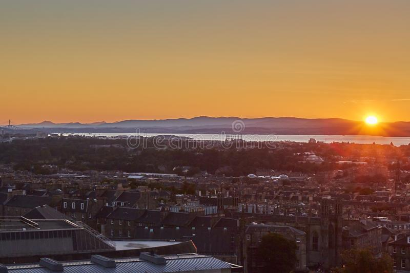Sun setting over horizon with Edinburgh cityscape in the foreground, Scotland, United Kingdom. royalty free stock photos