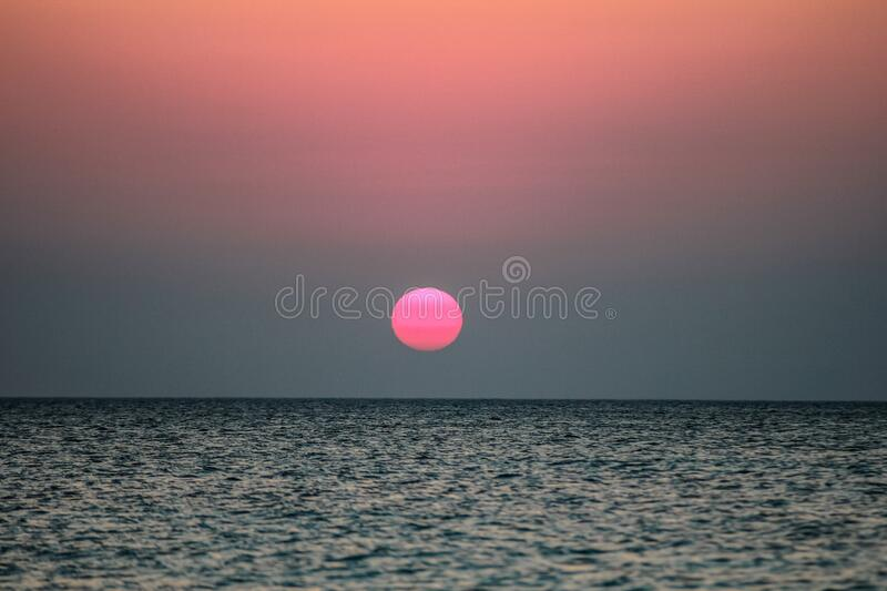 Sun setting over ocean royalty free stock photography