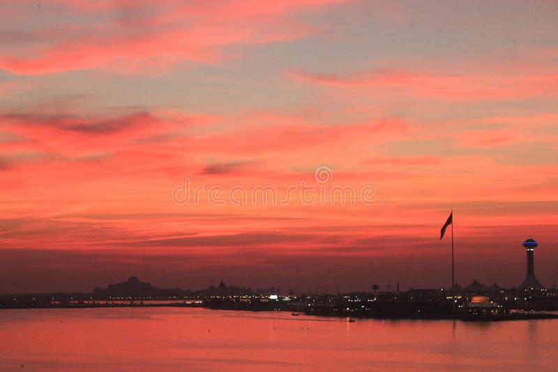 Sun setting over the ocean. With Middle Eastern backdrop. The sky and ocean are mirrored red from the sunset royalty free stock photography