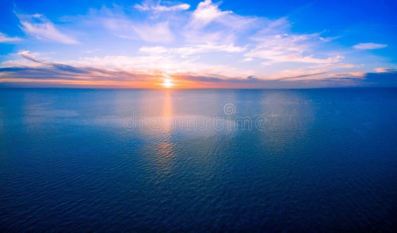 Aerial panorama of sun setting over ocean. Sun setting over ocean - minimalist sunset aerial panorama stock photo