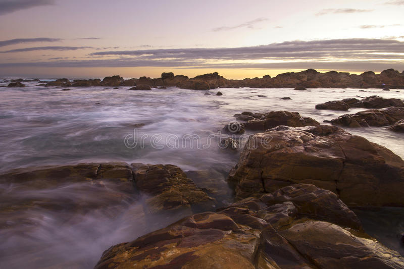Download Sun Setting Over Ocean And Rocks Stock Image - Image: 27200015