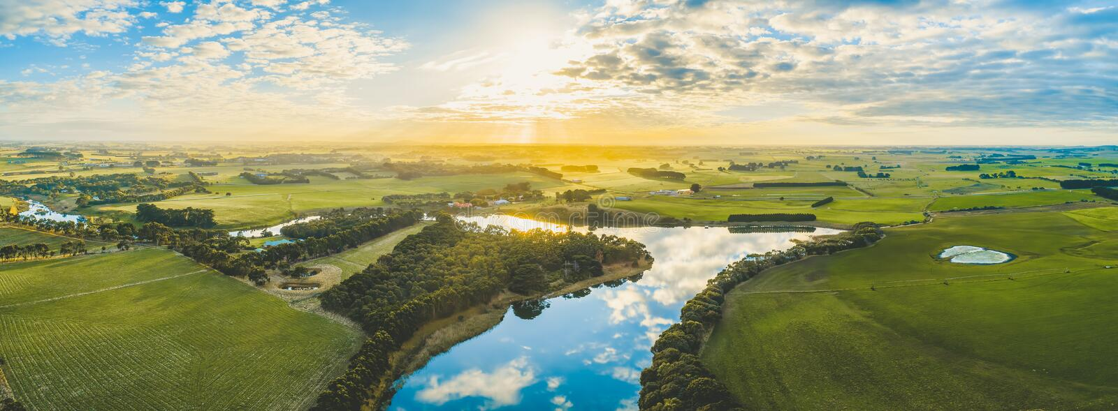 Sun setting over scenic Australian countryside grasslands and pastures with river passing through. stock image