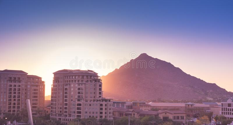 Sun setting over Scottsdale, Arizona. Waterfront area with Camelback Mountain glowing royalty free stock image