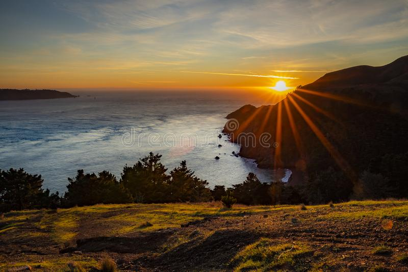Sun setting into the Pacific Ocean beyond San Francisco Bay, viewed from Marin Headlands in California, sun burst effect stock images