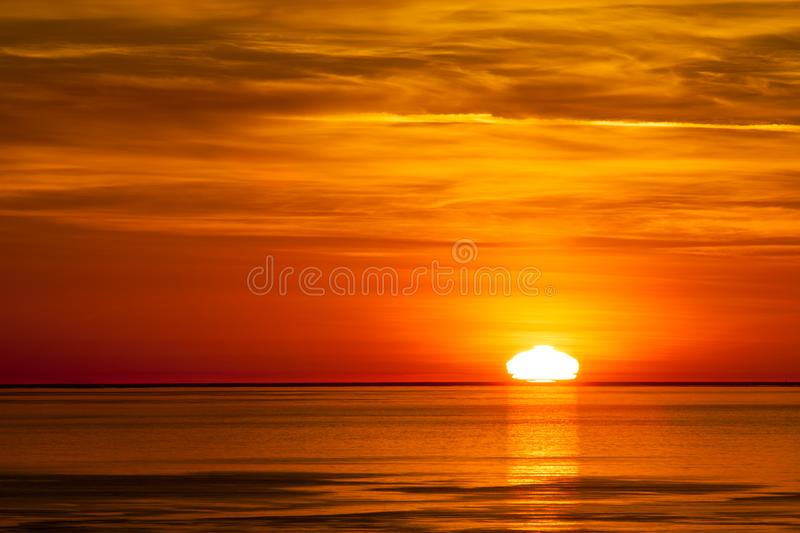 The sun setting in the pacific ocean stock image