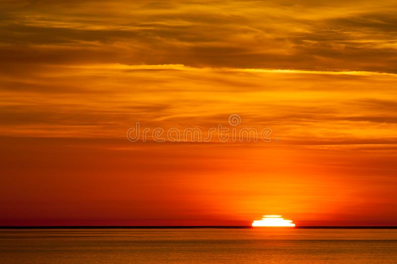 The sun setting in the pacific ocean stock images