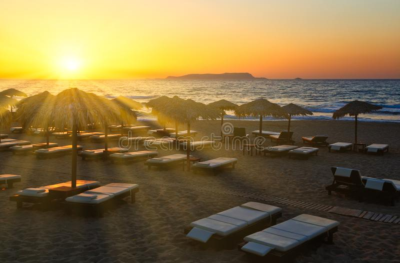 Sun setting in the sea on the horizon shines through rays of sun beds and umbrellas on the sandy beach of Europe, Crete stock images