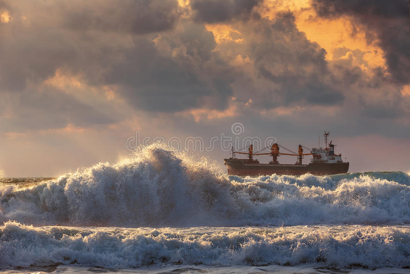 Sun Setting At The Sea With Sailing Cargo Ship Stock Photo ...
