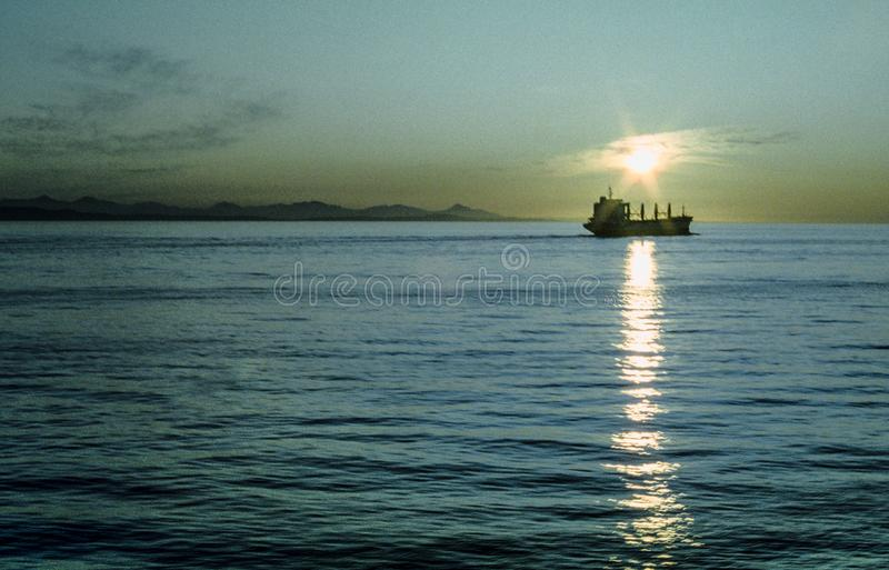 The sun is setting on a ship sailing in the Pacific Ocean royalty free stock image