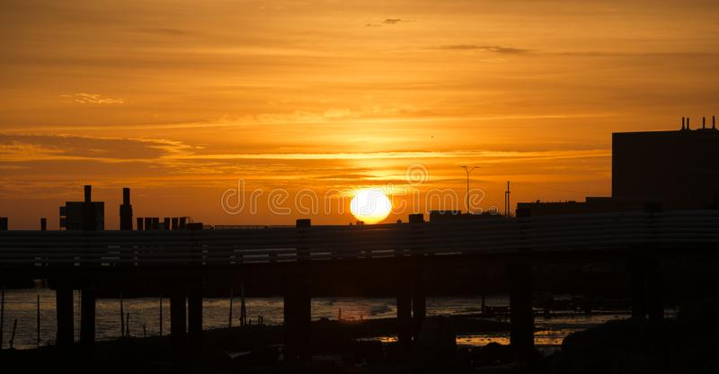 Sun setting silhouette on shore over pier and walkway stock photos