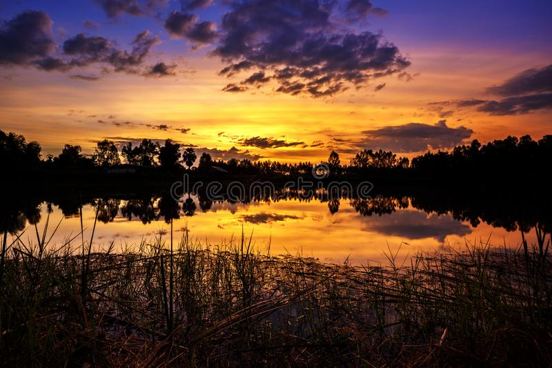 Sun setting with silhouette trees and bush around the big pond in rural of Thailand, shot taken by using long exposure therefore s. Mooth water surface stock photo