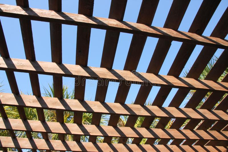 Sun and Shadow on a Pergola. Palm trees and blue sky show through a pergola creating shadows and an unusual design at Bird Island Park in Ponte Vedra Beach stock photography