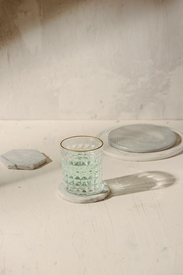 Sun shadow on the table with glass of water, marble plate.  stock photo