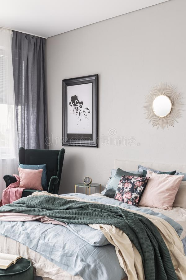 Sun shape like mirror and map in black frame on grey wall of fashionable bedroom interior with king size bed with cozy bedding royalty free stock photos