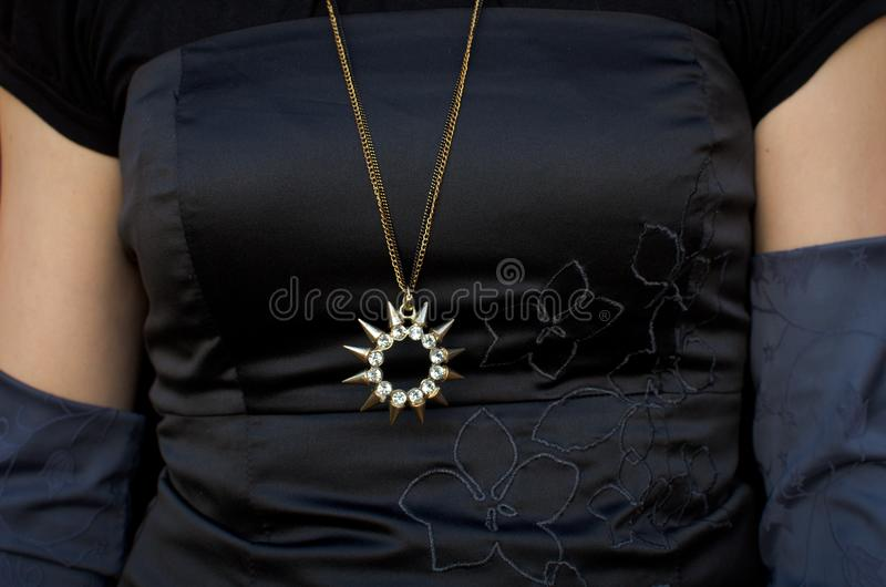Sun shaped necklace. Sun shaped piece of necklace on woman with black dress stock photos
