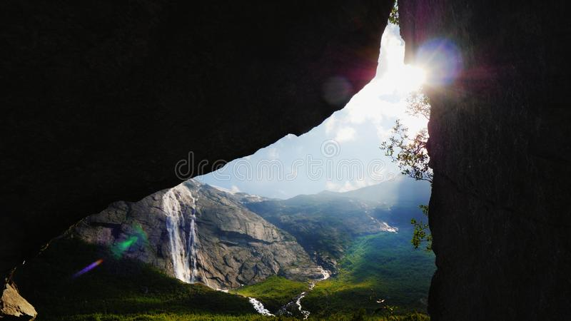 The sun shines through the arch in the rock, where you can see the picturesque valley surrounded by high mountains. The stock image