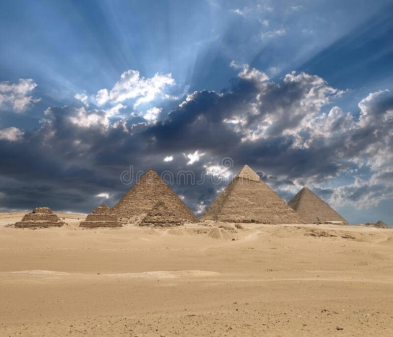 Sun shines from clouds above the Giza pyramid complex royalty free stock photos