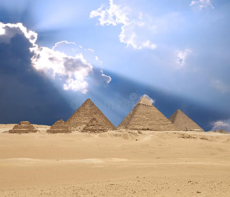 Sun shines from clouds above the Giza pyramid complex stock photography
