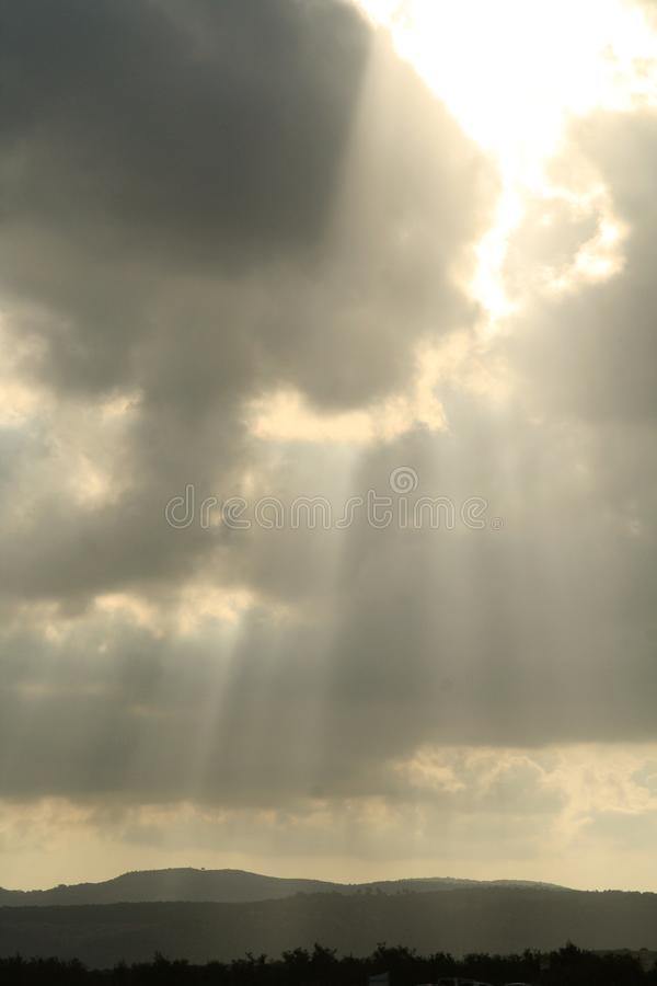 Sun shines through a cloudy sky over the mountains stock image