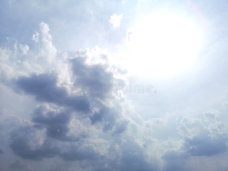The sun shines with a dark shadow behind the clouds nature background. Environment royalty free stock images