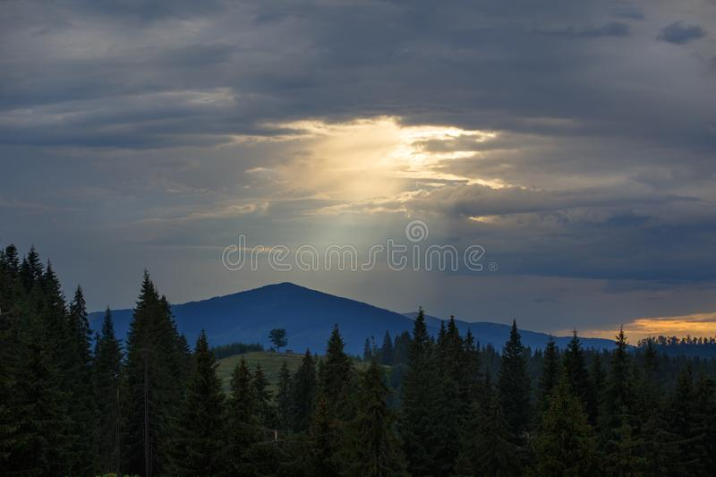 Sun shines through the gap in overcast dramatic sky over mountains royalty free stock photo