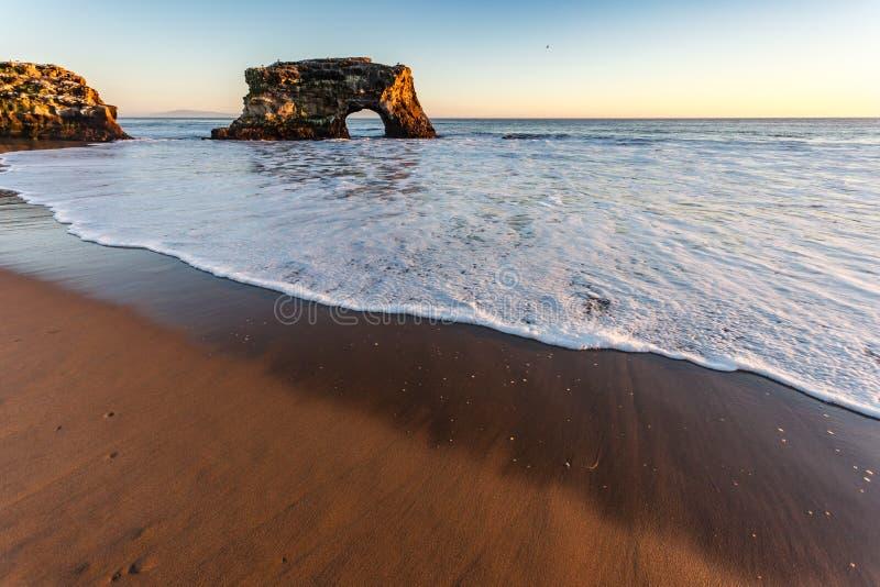 Natural Bridge in ocean on Santa Cruz coast in California at sunset royalty free stock images