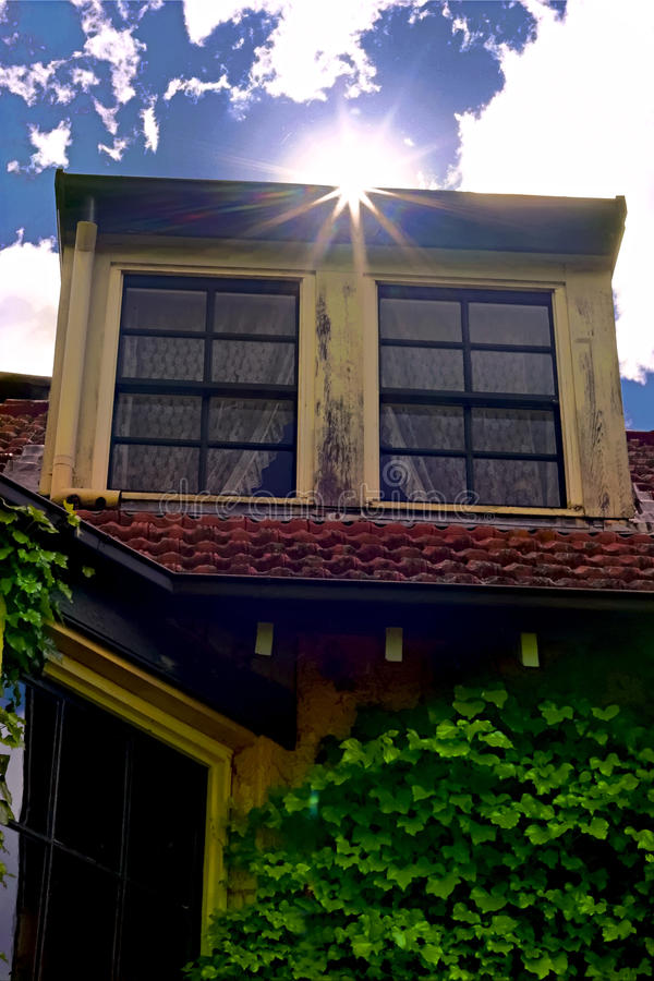 Sun shining from above a vintage garret. Sun beams shining from above a vintage garret. Tiled roof with a wooden garret. Old house exterior with vine and red stock images