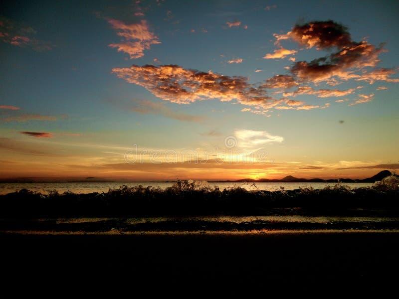 Sun shining behind the sea mountains of Vila da Gloria stock image