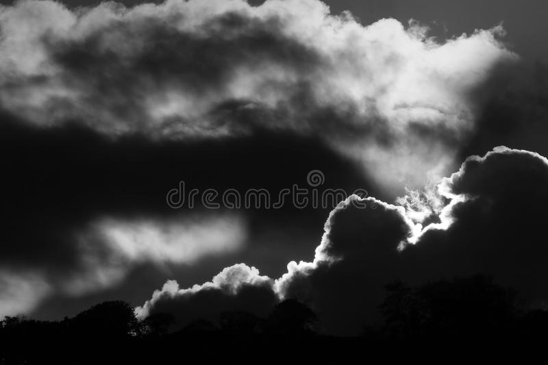 The sun behind clouds and trees stock photography