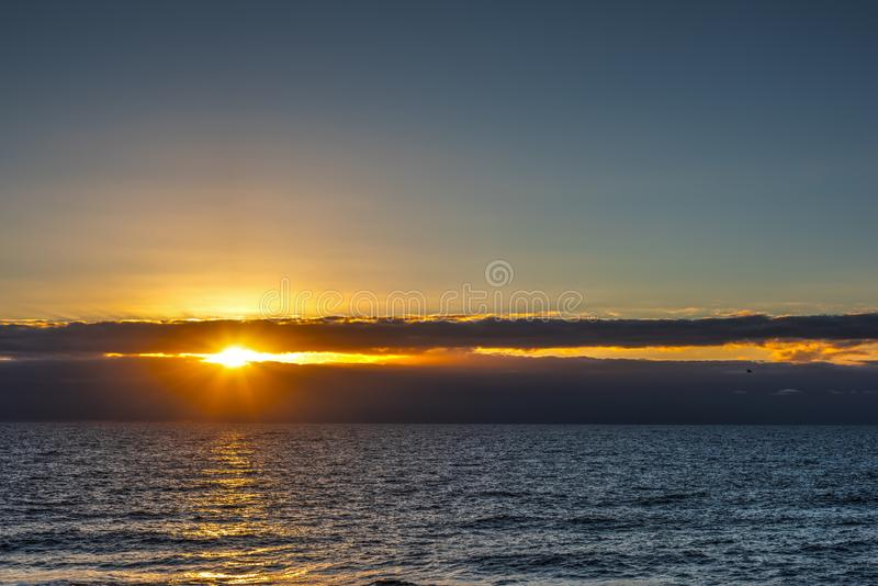 Sun shining through dark clouds over the sea at sunset. Sardinia, Italy stock images