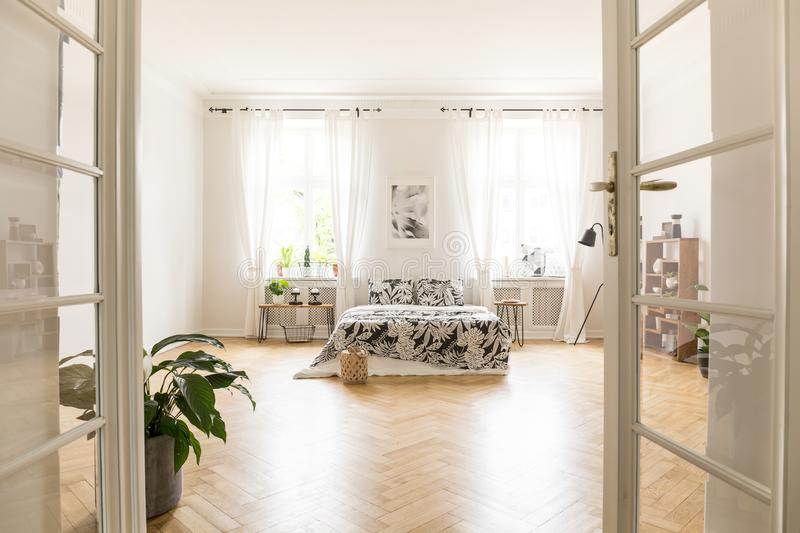 Sun shinning through windows into a spacious stylish bedroom interior in a villa. Big bed with bedding standing on herringbone par. Quet. Real photo. Empty floor royalty free stock photo