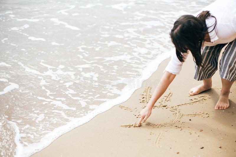 Sun sign on beach. Girl writing sun symbol text on sandy beach at sea waves. Hello summer concept. Summer Vacation, relax and royalty free stock photo