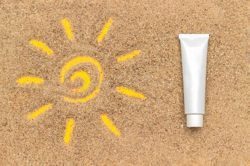 Sun sign drawn on sand and white tube of sunscreen. Template mockup for your design. Creative top view royalty free stock photography