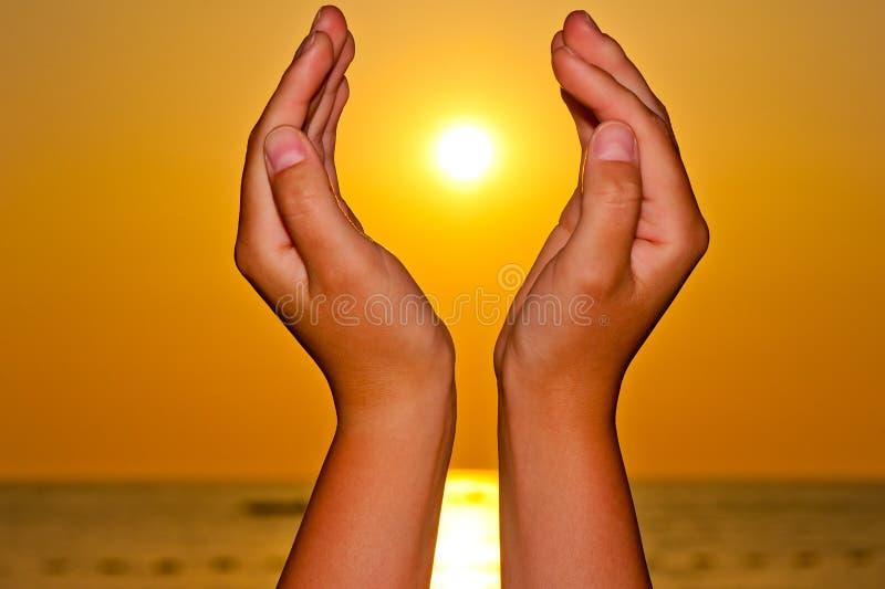 Sun sobre o mar nas mãos fotografia de stock