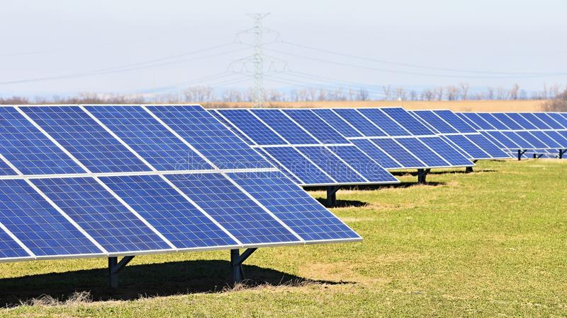 Sun and solar panels in a field. Solar energy power plant. Industrial and ecological concept for nature and eco / green technology. Solar panels in a field stock photography