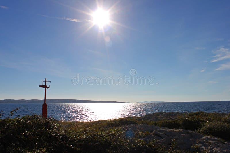 Sun sopra il mare Linea costiera alla spiaggia di Povljana sull'isola del PAG, Croazia Piccolo faro fotografia stock libera da diritti