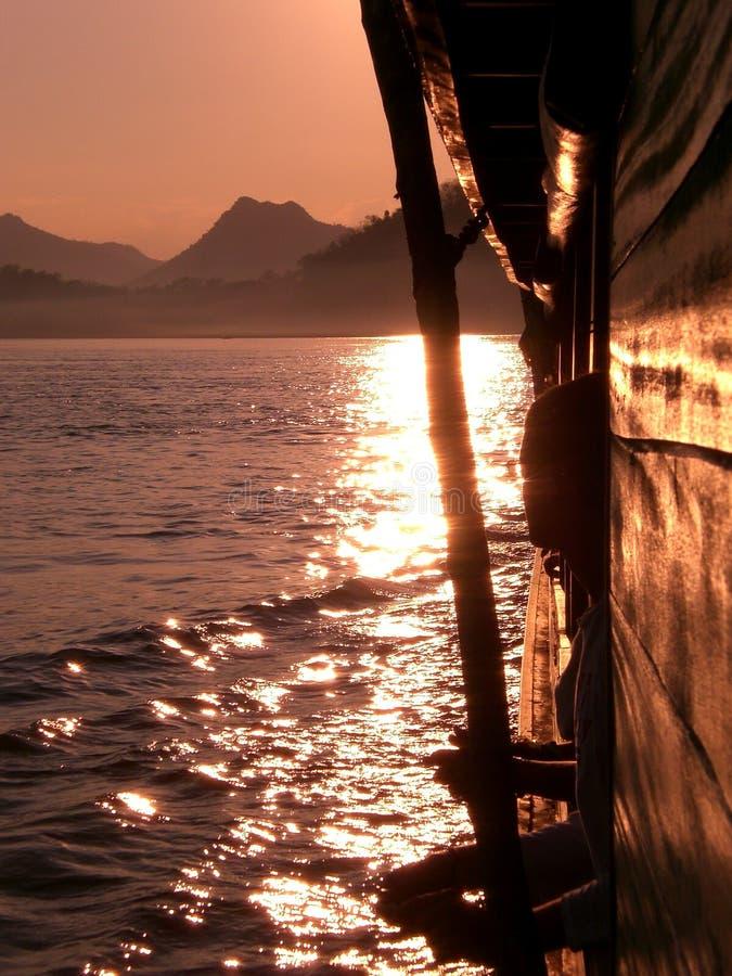 The Sun ställer in på Mekonget River royaltyfri bild