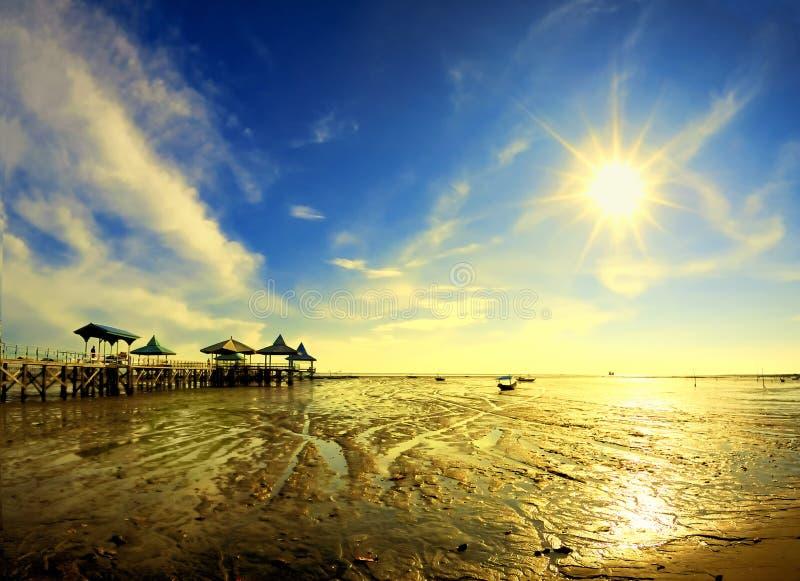 Sun star at morning on receding sea shore. Taken at Kenjeran beach, Surabaya, east Java, Indonesia stock photography