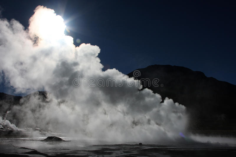 Sun through the steam of geyser. El Tatio is a geyser field located within the Andes Mountains of northern Chile at 4,200 meters above mean sea level. Tourists royalty free stock images