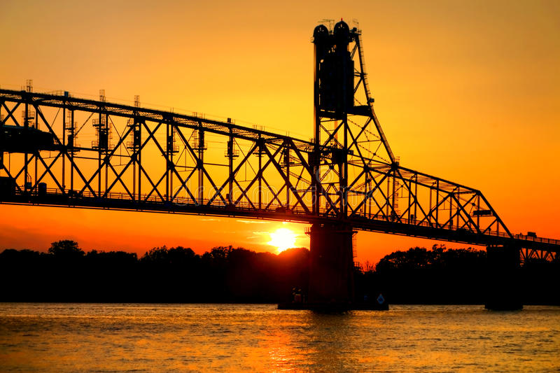 Sun by Steel Bridge Silhouette on River at Sunset. Setting sun over the horizon with silhouette of steel truss bridge with vertical lift span on the Delaware royalty free stock photo