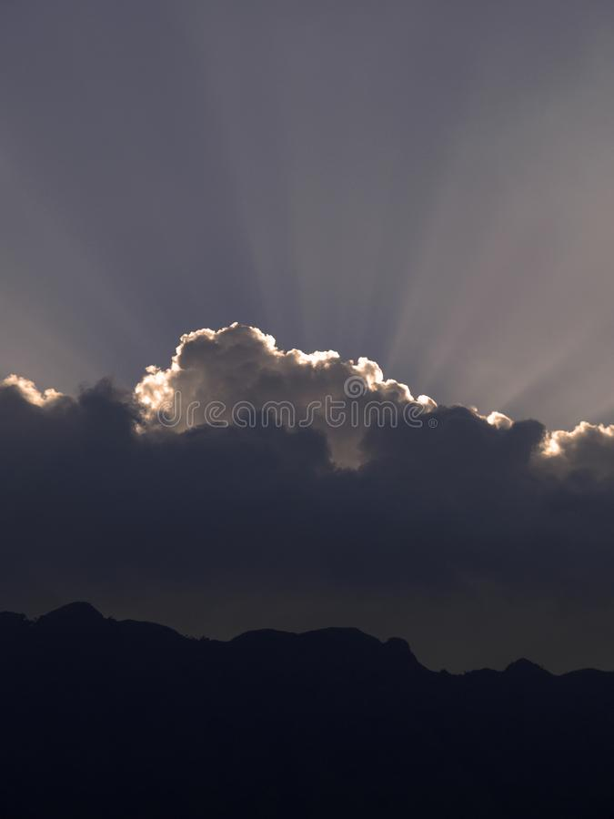 Sun-Strahlen von hinten Hügel und Wolken stockfotos