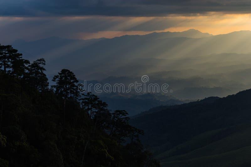 Sun strahlt das Brechen durch die Wolken über einer Berglandschaft aus stockbilder