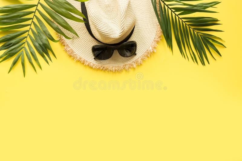 Sun straw beach hat with eyeglasses and tropical palm on yellow. Summer vacations concept. Top view stock image