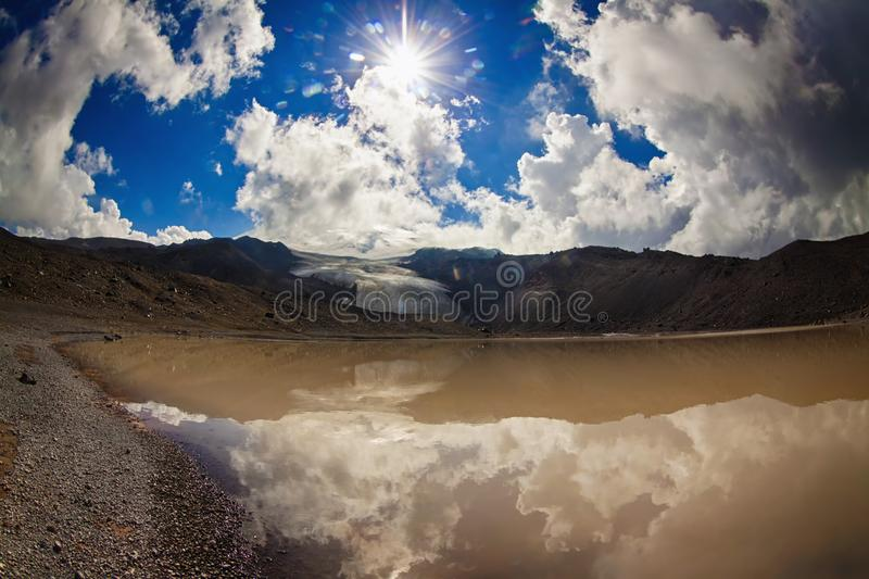 Sun and sunbeams high in the cloudy sky over the lake. In the mountains with cliff and glacier. View from high altitude royalty free stock photo