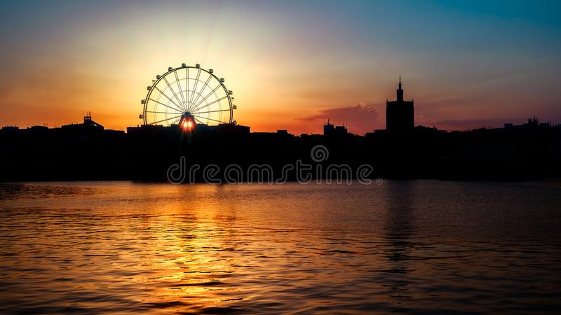 The sun at sunset through ferris wheel. At Malaga city, Costa del Sol, Andalucia, Spain, Western Europe royalty free stock photography