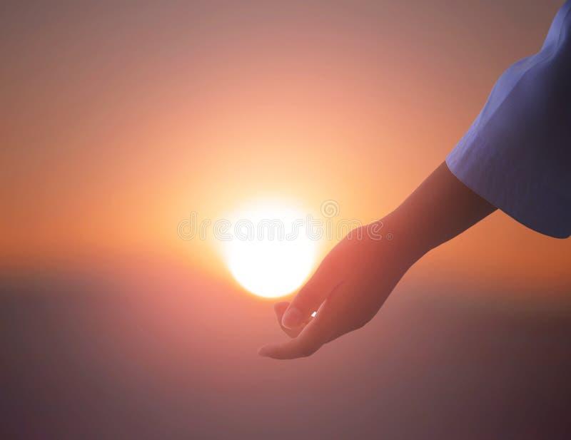 Sun sur la main femelle Silhouette de main tenant le soleil image stock