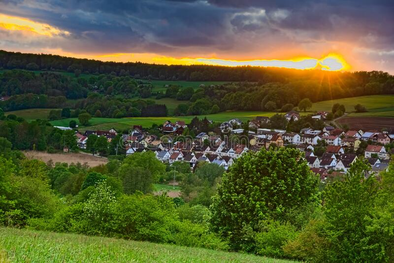 A picturesque sunset over a small village in Germany. The sun is about to set and illuminates the sky in bright orange. A thick cloud cover and strong colors stock photography