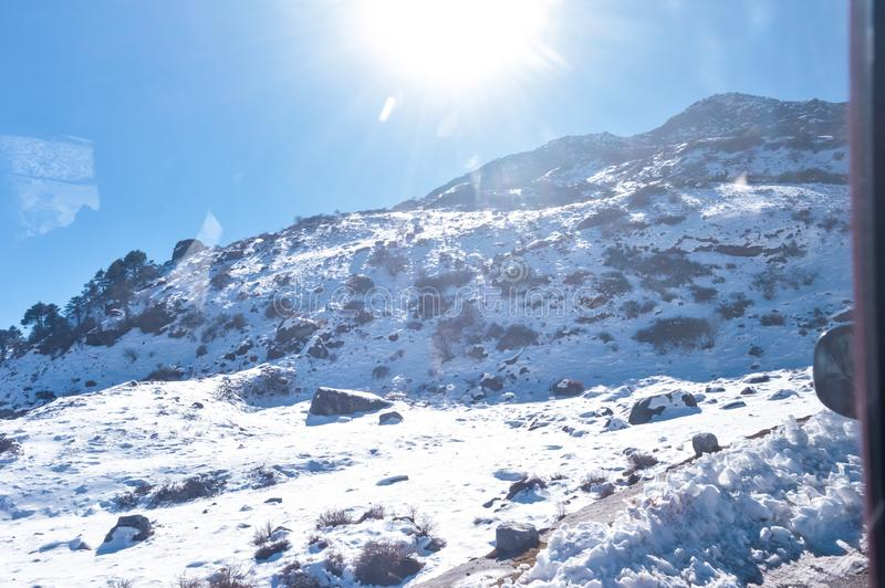 Sun on top of snow cover himalaya range. Frozen Rocky peak filled with deep snow illuminate rising sunlight in frosty winter day. Time. Blue clear sky. No Cloud royalty free stock images